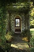 Begrünter Pavillon mit gepflastertem Weg im Garten