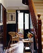 Korbstuhl neben offener Haustür im traditionellen Treppenhaus