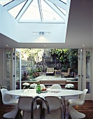 A dining table with white Bauhaus bucket chairs in front of open terrace doors