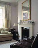 A brown leather armchair and a white sofa in front of a fireplace with a mirror above it