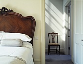 An antique bed next to an open door and a view of a chair in a hallway