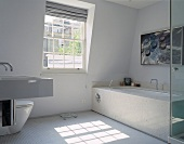 A white designer bathroom with stone tiles on the bathtub and white mosaic floor tiles