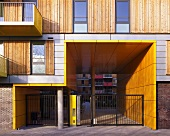 A modern apartment block with sliding wooden elements next to the windows and a yellow panelled entrance way