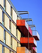 A modern apartment block with coloured balconies and sliding wooden elements