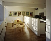 An open-plan kitchen with a dining table and Thonet chairs in front of a white kitchen counter