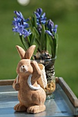 A clay rabbit figure in front of purple hyacinths in a glass