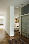 A modern hallway with parquet flooring an an open bedroom door