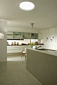 A white designer kitchen with a monolithic kitchen counter and mosaic tiles under a glass dome