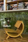 Holzsessel im Designerstil vor Fenster mit Blick in Innenhof auf Pflanzen
