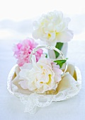 Peonies on a lace cloth in a silver bowl