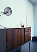 A sideboard dating from the late 1960s with a designer lamp