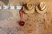 Straw hats and a glass heart on an old row of hooks