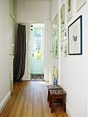 Flur mit Holzdiele und Vorhang vor der Eingangstür in einem schwedischen Haus