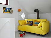 A yellow sofa in an attic room