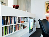 A white shelf for books and the television