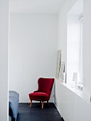 A red chair in the corner of a room