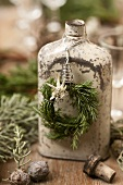 An old hip flask hung with a wreath of rosemary and edelweiss