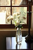 White roses in a vase next to a table lamp (Nabygelen, Wellington, Western Cape, South Africa)