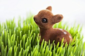 A fawn toy in dewy grass