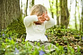 A little child sitting on the forest floor hiding his face from the camera