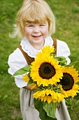 Little girl in traditional costume holding a bouquet of sunflowers