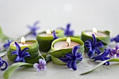 Tea lights wrapped in leaves and decorated with hyacinth flowers