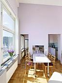 Ein langer Esstisch mit Stühlen vor dem Fenster in einem Esszimmer in Doppelhöhe