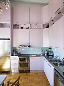 A modern kitchen with high cupboards and fitted appliances