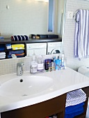 A white washstand and bathing utensils in a bathroom
