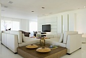 An elegant living room with seats, a coffee table and a flat screen television