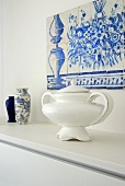 A soup tureen and vases on a shelf with an azulejo made of blue and white ceramic tiles above it