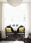 Two black armchairs in front of a Georgian bay window with white curtains
