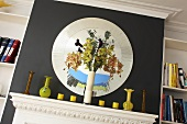 A vase on a white mantelpiece and a round mirror set into the black chimney breast