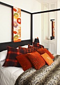 Decorative cushions on a bed on a four poster bed