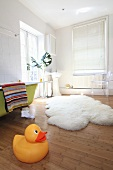 A giant rubber duck and a sheepskin rug on a the floor in a bathroom with a green, free-standing bathtub