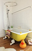 A giant rubber duck in front of a yellow bathtub with a shower and a shower curtain