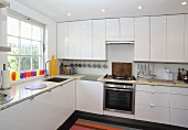 An L-shaped kitchen with white cupboards