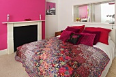 A double bed with decorative cushions and a quilt in a bedroom with pink and white walls