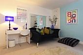 Decorative cushions on a dark blue sofa, a floor cushion and a white desk in a living room
