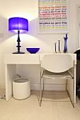 Ein weisser Tisch mit einer Lampe und einem Stuhl