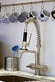Tassen hängen an Haken über der Küchenarmatur