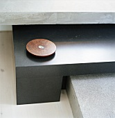 A tealight in a flat round candle holder on a sideboard