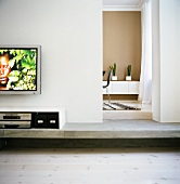 A flat screen television on the wall and multimedia devices in a sideboard