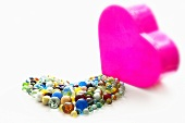 Colourful glass marbles in the shape of a heart next to a pink heart-shaped chocolate box