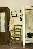 A chair, coat hooks and a clothes rail in a hallway