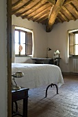 A view into a bedroom with a terracotta floor and a wood beam ceiling