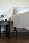 A bedside table next to a high bed with white bedclothes