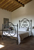 A wrought iron bedstead in a bedroom