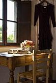 Ein rustikaler Holzschreibtisch mit Stuhl vor dem Fenster