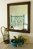 Fruit in a blue bowl and an antique bottle holder in front of a mirror reflecting a blue wrought iron bed